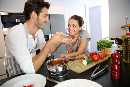 Photo pour Mari et femme, dégustation de plat de pâtes en cuisine - image libre de droit