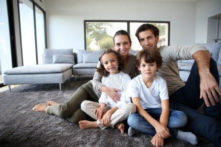 Photo for Happy family portrait at home sitting on carpet - Royalty Free Image