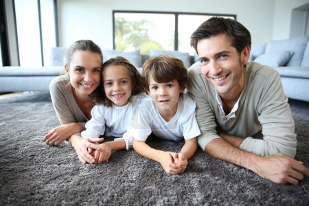 Photo for Smiling family at home on carpet - Royalty Free Image