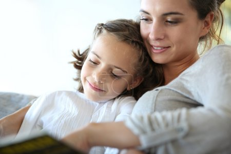 Photo for Mom with little daughter reading book in sofa - Royalty Free Image