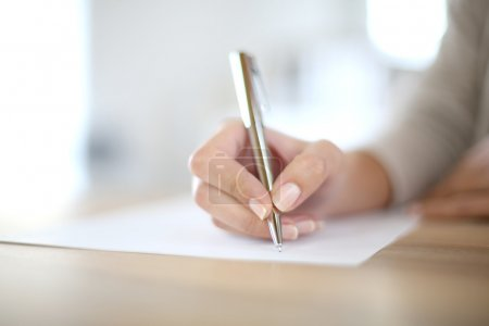 Photo pour Gros plan de l'écriture de la main de la femme sur papier - image libre de droit