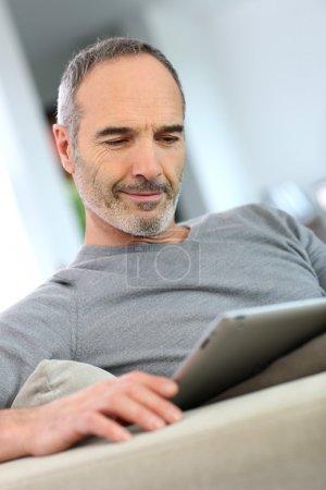 Photo pour Homme d'âge mûr à la maison en regardant tablet - image libre de droit