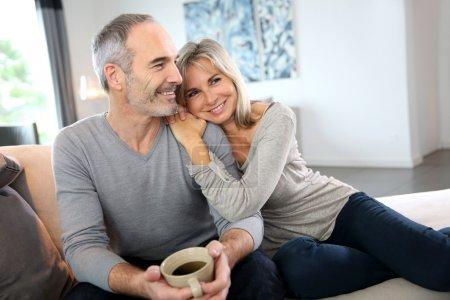 Photo pour Couple de personnes âgées romantique détente sur canapé - image libre de droit