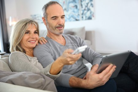 Woman watching tv and man using tablet