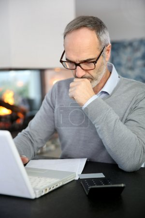 Mature man working with laptop
