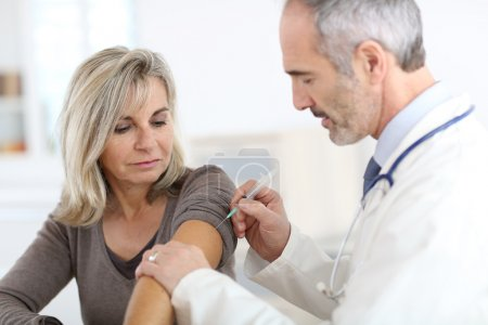 Doctor injecting vaccine