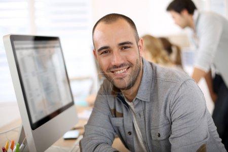 Photo pour Joyeux gars assis en face de l'ordinateur de bureau - image libre de droit
