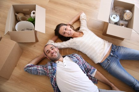 Photo for Young couple lying on floor in new home - Royalty Free Image