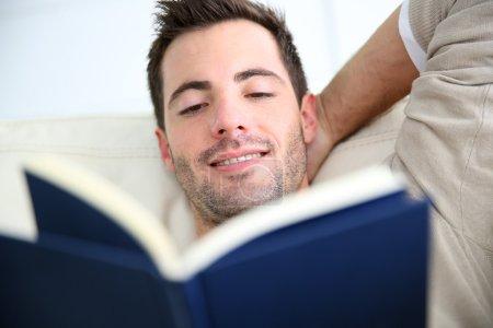 Man in sofa reading book