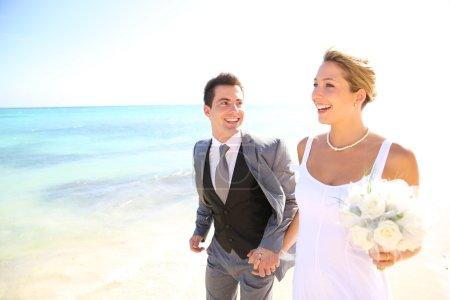 Photo pour Couple marié marchant sur la plage - image libre de droit