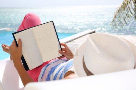 Photo pour Livre de lecture femme détendu dans la chaise longue - image libre de droit