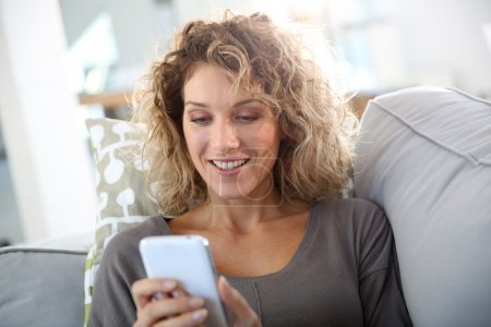 Photo for Smiling woman relaxing in sofa with smartphone - Royalty Free Image