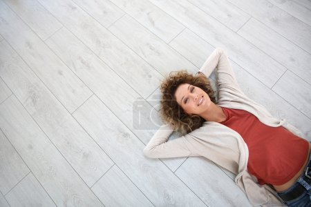 Photo for Woman laying on wooden modern flooring - Royalty Free Image