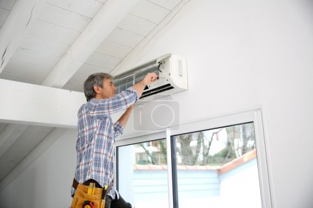 Photo for Repairman fixing air conditioner unit - Royalty Free Image