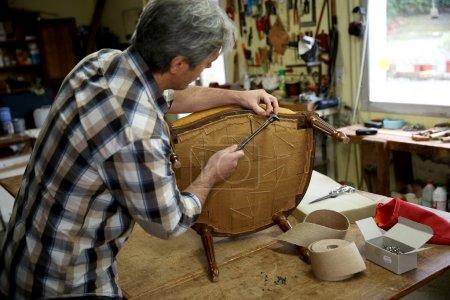 Craftsman repairing armchair