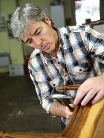 Photo for Craftsman repairing antique armchair in workshop - Royalty Free Image