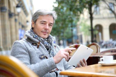 Photo pour Homme mûr assis à la table de café avec tablette - image libre de droit
