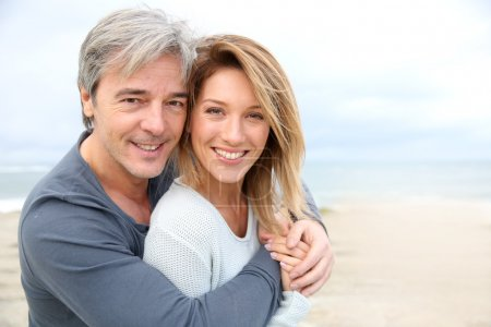 Photo for Cheerful mature couple embracing by the beach - Royalty Free Image