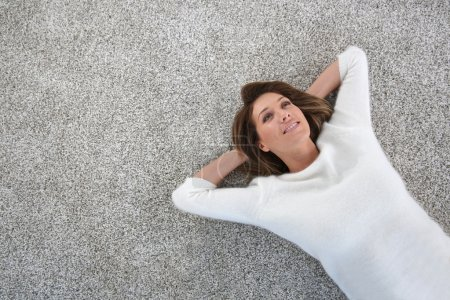 Photo for Upper view of mature woman relaxing on carpet at home - Royalty Free Image