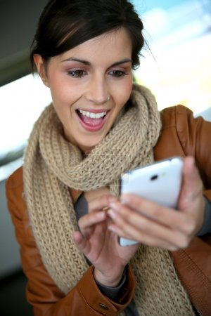 Smiling girl using smartphone