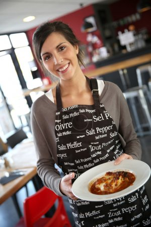 Photo for Cheerful young waitress serving dish to customers in restaurant - Royalty Free Image
