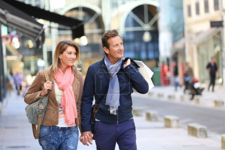 Photo for Middle-aged couple doing shopping on week-end, bags on shoulder - Royalty Free Image