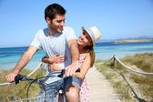 Uomo dando in bicicletta alla ragazza