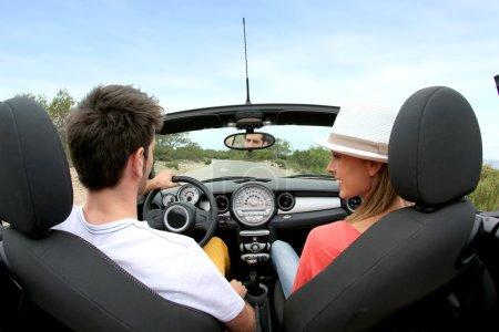 Couple driving convertible car