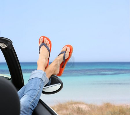 Photo for Closeup of woman feet by convertible car window - Royalty Free Image