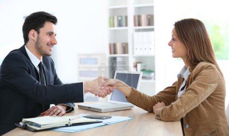 Woman giving handshake to adviser