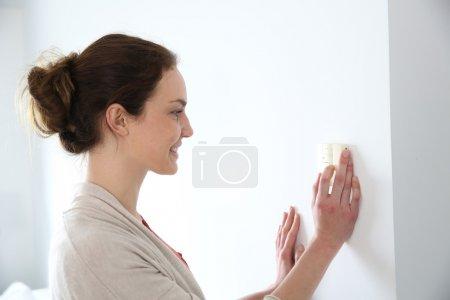 Woman programming temperature inside home...