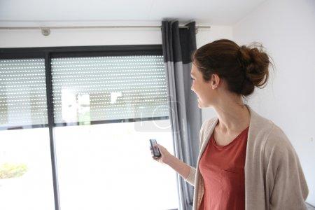 Photo pour Femme à l'aide de la télécommande pour ouvrir l'obturateur électrique - image libre de droit