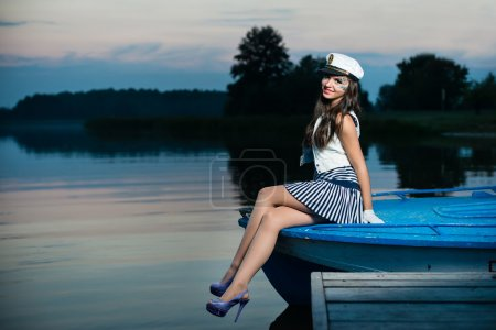 Young beautiful sailor woman sitting on the boat