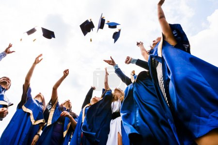 Photo for Image of happy young graduates throwing hats in the air - Royalty Free Image