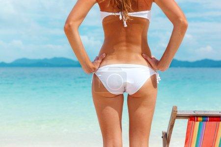 Cropped image of sexy woman in white bikini on beach