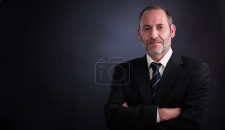 Photo for Successful senior executive businessman smiling into the camera - Royalty Free Image