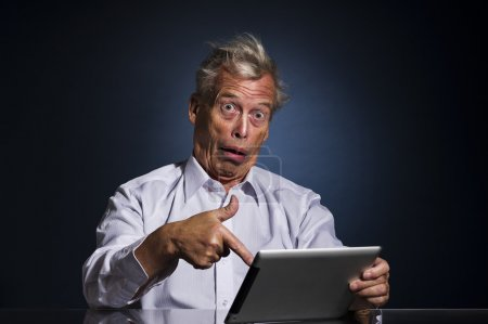 Shocked senior man pointing to his tablet