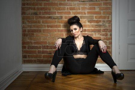 Moody elegant woman sitting on a parquet floor