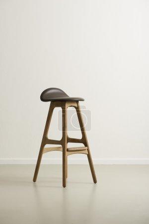 Photo pour Tabouret de bar moderne en bois haut avec assise en cuir noir et repose-pieds sur un sol réfléchissant dans une pièce vide avec un mur blanc, format vertical avec espace de travail en plein jour - image libre de droit