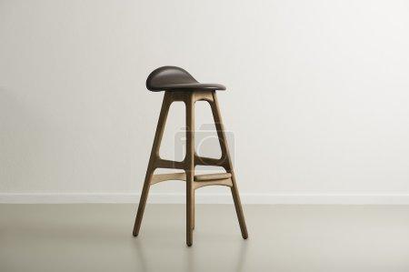 Photo pour Tabouret de bar en bois avec assise en cuir moulé centrée dans une pièce vide minimaliste avec un mur blanc et un espace de copie, format horizontal - image libre de droit