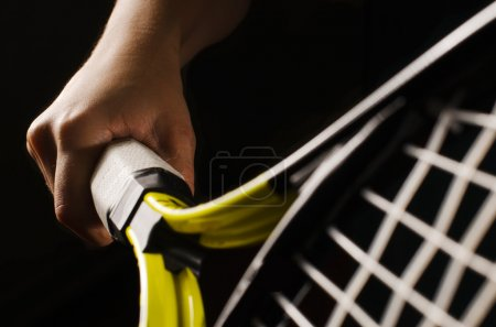 Photo for Hand on grip and swinging a tennis racket. Isolated on black background. - Royalty Free Image