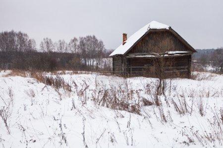 Casa abandonada en pueblo cubierto de nieve