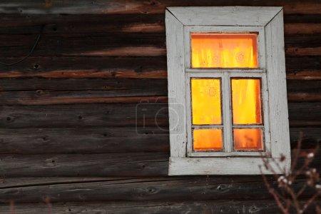 Iluminación ventana de casa de madera rural