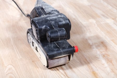 hand-held belt sander sanding wooden surface