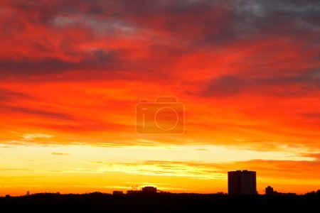 Dramatic bright red, yellow, blue clouds in sunris...