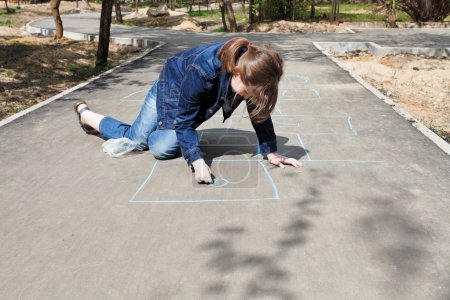 Photo for Girl drawing hopscotch outdoors in sunny day - Royalty Free Image
