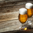 Two glass beer on wood background with copyspace...