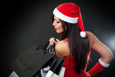 Girl wearing santa claus clothes with shopping bag