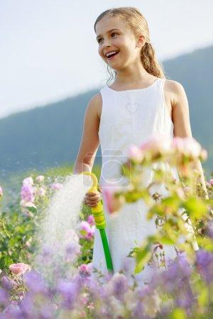 Watering, flower garden - beautiful girl watering roses