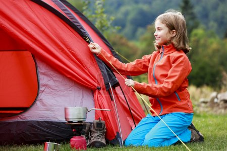 Camp in the tent - young girl setting a tent on the camping